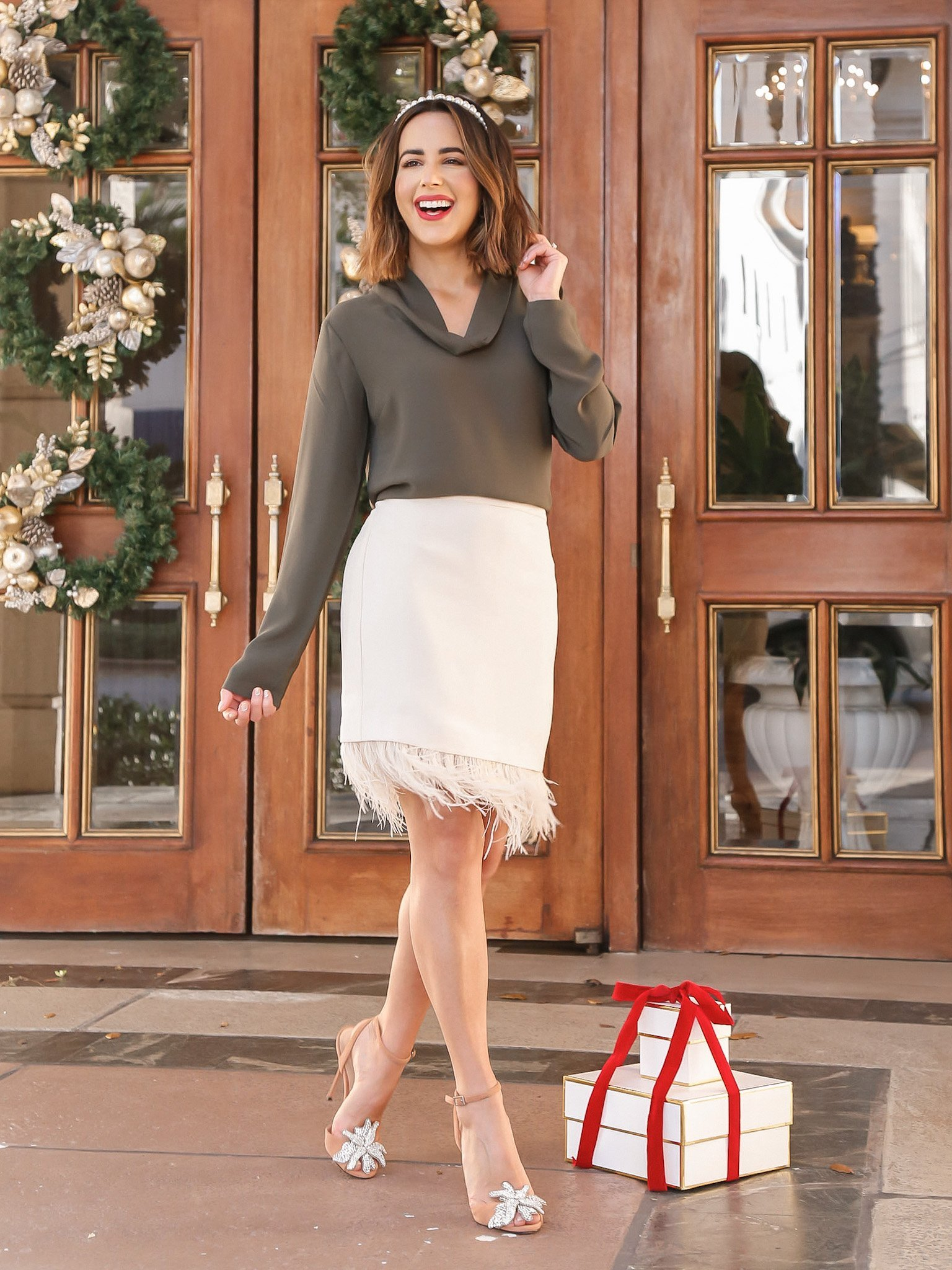 kelly saks wearing holiday outfit featuring green silk blouse and ivory skirt with feathers.