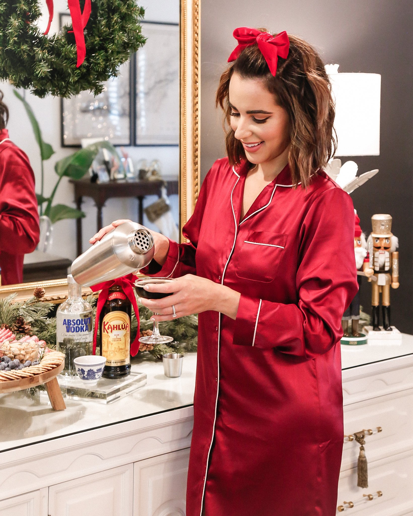 hostess mixing cocktails at holiday party wearing red silk sleep shirt pajama